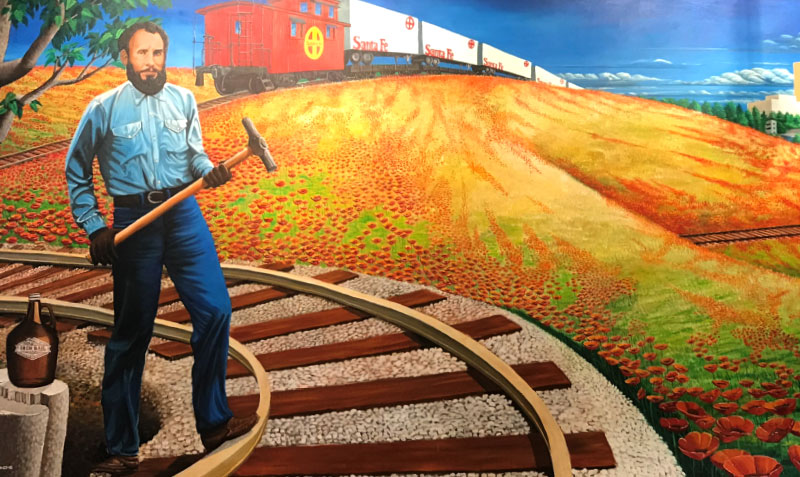 Iron Rail Pale Ale - Painted by Andy Valdivia, this mural shows Cyrus K Holliday as a gandy dancer in the early days of the AT&SF.  With nods to the Wizard of Oz, this mural shows the Capital City as the land of Oz.